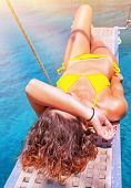 Sexy woman tanning on sailboat, female relaxing above transparent blue sea, girl enjoying bright sun light, active lifestyle, happy summer vacation