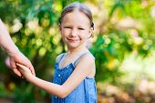 Portrait of adorable little girl outdoors on summer day holding her father hand