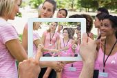 Composite image of hand holding device showing photograph of breast cancer activists