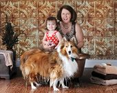 A mature woman with her granddaughter and pet.  They've been washing the beautiful collie in a small, copper tub.  He's standing in front of it with feet and lower fur dripping wet.