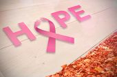 Breast cancer awareness message against autumn leaves against white wood