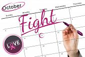 Businesswomans hand writing with marker against breast cancer awareness message on poster