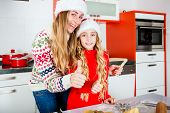 Mother and daughter baking X-mas cookies at home in domestic kitchen