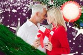 Loving couple with gift against snowflake wallpaper pattern
