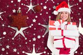Festive blonde holding pile of gifts against snowflake wallpaper pattern