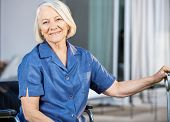 Portrait of happy senior woman sitting on wheelchair at nursing home yard