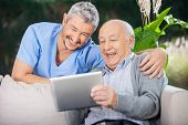 foto of nursing  - Male nurse and senior man laughing while looking at digital PC at nursing home porch - JPG
