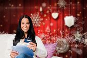 Woman sitting with tablet pc against blurred christmas background