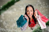 Woman standing with shopping bags against blurry christmas scene