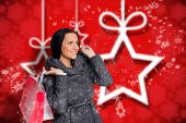 Smiling woman holding shopping bag against blurred christmas background