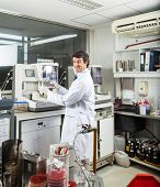Portrait of confident male scientist analyzing urine samples in laboratory