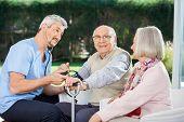Woman looking at male doctor measuring blood pressure of senior man at nursing home