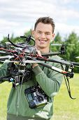 Portrait of happy young engineer holding UAV helicopter in park