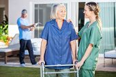 Smiling disabled senior woman and nurse looking at each other in lawn at nursing home