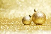 Two decorative christmas balls on golden background