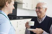 Nurse Chatting With Senior Man During Home Visit