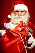 Generous Santa Claus holding big red sack with giftboxes and toys