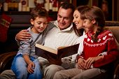 Cheerful family of four reading together on Christmas evening