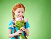 Adorable girl looking at bunch of tulips in her hands