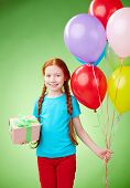 Pretty girl with giftbox and balloons having birthday