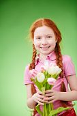 Adorable girl with bunch of tulips over green background