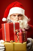 Santa Claus with pile of gifts looking at camera over eyeglasses