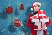 Smiling woman holding christmas presents against snowflake wallpaper pattern