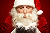 Santa Claus in eyeglasses blowing snow from his palms