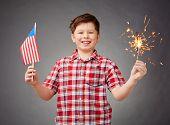Joyful boy holding bengal light and American flag
