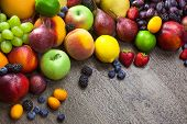 Mixed fresh Fruits on the  wooden background  with water drops and copy space