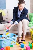 pic of toy phone  - Young woman working from home and cleaning up toys - JPG
