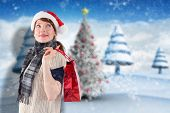 Smiling woman wearing santa hat against blurry christmas scene