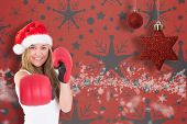 Festive blonde punching with boxing gloves against snowflake wallpaper pattern
