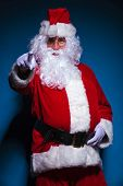 Picture of a Santa Claus pointing at the camera, against blue background.