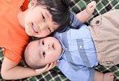 image of little sister  - Cute little sister and baby laying on the bed fun - JPG