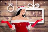 Woman smiling with hands raised against blurred christmas background