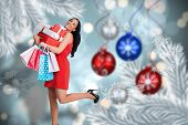 Woman standing with shopping bags against baubles hanging over christmas scene