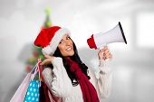 Woman holding some shopping bags against blurry christmas tree in room