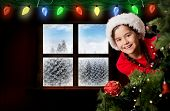 Festive girl looking from behind christmas tree against fir tree forest in snowy landscape