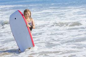 foto of boogie board  - Cute little girl boogie boarding in the ocean - JPG