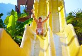 image of excite  - excited man having fun on water slide in tropical aqua park - JPG