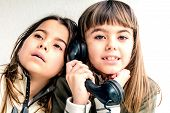 stock photo of conversation  - Seven year old girl talking on the old vintage phone and her sister eavesdropping her conversation. White background.