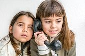 pic of 7-year-old  - Seven year old girl talking on the old vintage phone and her sister eavesdropping her conversation. White background.
