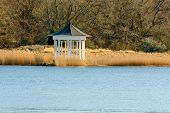 image of early spring  - White open gazebo by the water in early spring - JPG