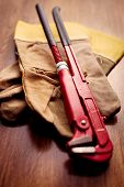 foto of pipe wrench  - Close up Red Pipe Wrench on Top of a Brown Hand Gloves Above the Wooden Table - JPG