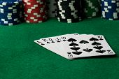 pic of flush  - spades straight flush with poker chips on green table - JPG