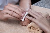 stock photo of nail  - Woman in nail salon is receiving manicure by beautician - JPG