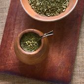 picture of mating  - South American yerba mate tea in a wooden mate cup with strainer called bombilla photographed with natural light - JPG