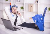 picture of fin  - Happy businessman is working in office is wearing in fins - JPG