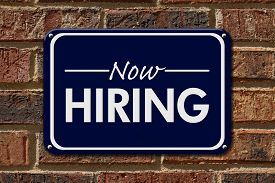 stock photo of arrow  - Now Hiring Sign A blue sign with the word Now Hiring with an arrow on a brick wall - JPG